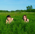 Girls lay in a green summer grass Royalty Free Stock Photography