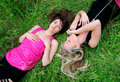 Girls laying in grass Stock Images