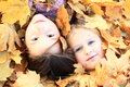 Girls in leaves two little kids covered by dead yellow maple Royalty Free Stock Photography