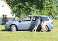 Girls leaving a car barefoot girl opening door of silver for her sister getting out Royalty Free Stock Photos