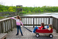 Girls looking at park lake with outdoor dump cart children and pointing Royalty Free Stock Photos