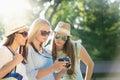 Girls looking at photos on their camera at summer holidays Royalty Free Stock Photo