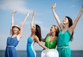 Girls looking at the sea with hands up summer holidays and vacation on beach Stock Photo