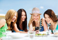 Girls looking at smartphone in cafe on the beach summer holidays vacation and technology Royalty Free Stock Images