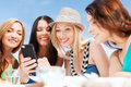 Girls looking at smartphone in cafe on the beach summer holidays vacation and technology Royalty Free Stock Photos