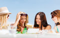 Girls looking at tablet pc in cafe summer holidays vacation internet and technology Royalty Free Stock Photo