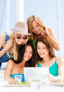 Girls looking at tablet pc in cafe summer holidays vacation internet and technology Royalty Free Stock Images