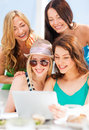 Girls looking at tablet pc in cafe summer holidays vacation internet and technology Stock Images