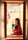 Girls looking into window three little opened wooden Stock Image