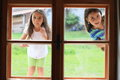 Girls looking into window two little wooden Stock Images