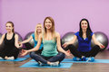 Girls meditate to restore strength and breath group of young women in the gym centre yoga attractive young people fitness sport Royalty Free Stock Photo