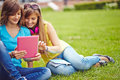 Girls networking friendly with touchpad on green lawn Royalty Free Stock Images