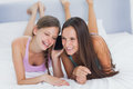 Girls on the phone at girls night in home lying bed Royalty Free Stock Photo