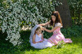 Girls playing dressup two young play in the garden sunlight Stock Image