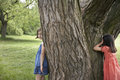 Girls playing hide and seek by tree two in park Stock Images
