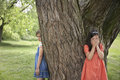 Girls playing hide and seek by tree two in park Royalty Free Stock Photos