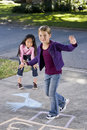 Girls playing hopscotch Royalty Free Stock Photos