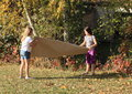 Girls playing with paper two big leaf of Royalty Free Stock Photos