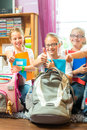 Girls prepare bags for school with books or sisters packing schoolbags text next day Stock Photography