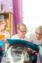 Girls prepare bags for school with books or sisters packing schoolbags text next day Stock Photo