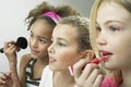 Girls putting on makeup and lipgloss closeup side view of three side by side Stock Images