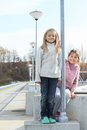 Girls on railing of dam two little kids concrete a by a lamp Royalty Free Stock Photography