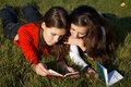 Girls reading the books on the lawn Stock Photography
