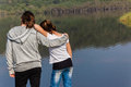 Girls river lagoon two young together looking over the smooth glass waters and swamp vegetation of by the beach shoreline Stock Images