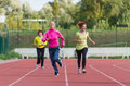 Girls running womens jogging on athletics track Stock Images