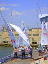 Girls sailing boats racers sailors descend a boat into water for the regatta and many at the quay ready for the race of the junior Royalty Free Stock Image