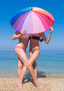 Girls at the sea two young women hiding under iridescent parasol Royalty Free Stock Images