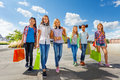 Girls with shopping bags walking together on road stoned and smile happily urban background in summer during daytime Royalty Free Stock Photos