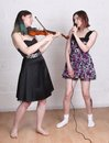 Girls singing and playing violin two teenage a Stock Image
