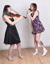 Girls singing and playing violin two teenage one a the other Stock Image