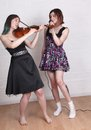 Girls singing and playing violin two teenage one a the other with a microphone Stock Photography
