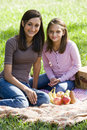 Girls sitting on picnic blanket on grass in park Royalty Free Stock Photo