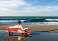 Girls sitting on a red bench on the beach rear view of and looking at sea Stock Photo