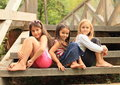 Girls sitting on stairs three barefoot wooden Royalty Free Stock Image