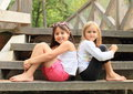 Girls sitting on stairs two barefoot wooden Royalty Free Stock Image