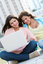 Girls social networking on a laptop happy outdoors Royalty Free Stock Photography