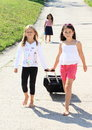 Girls with suitcase leaving their sister two barefoot black chech in baggage sad Stock Photography