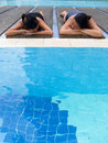 Girls sun tanning at Pool Stock Images