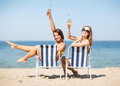 Girls sunbathing on the beach chairs summer holidays and vacation and drinking Stock Photos