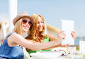 Girls taking photo in cafe on the beach summer holidays vacation and technology with tablet pc Royalty Free Stock Photos