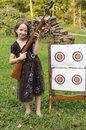 Girls target shoot smiling young girl in dress holds a bb gun and stands next to her bulls eye targets Royalty Free Stock Images