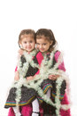 Girls in tinsel portrait of sisters wrapped up with christmas tree Royalty Free Stock Images