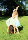 Girls training handstand exercising barefoot girl with long hair dressed in dress is trainging while second kid is holding her Royalty Free Stock Images