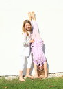 Girls training handstand exercising barefoot girl with long hair dressed in white clothes is trainging while second kid is holding Royalty Free Stock Photos