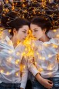 Girls twins with lights. New year`s eve. Christmas. Cozy holiday at the fir-tree with lights and gold decor