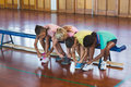 Girls tying shoe laces in basketball court Royalty Free Stock Photo